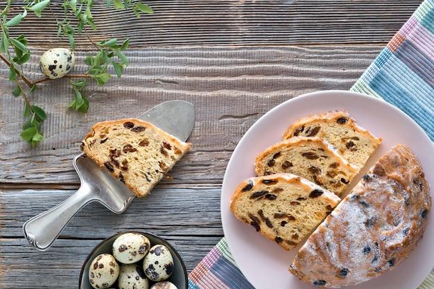 Chleb wielkanocny (osterbrot po niemiecku). odgórny widok tradycyjny fruty chleb na nieociosanym drewno stole z świeżymi liśćmi i przepiórek jajkami.
