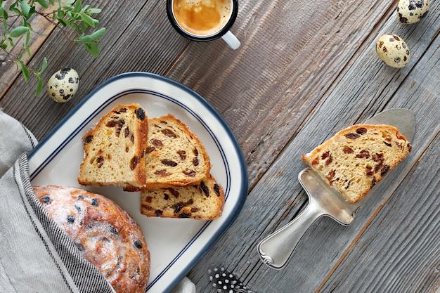 Chleb wielkanocny (osterbrot po niemiecku). odgórny widok tradycyjny owocowy chleb na nieociosanym drewnie z świeżymi liśćmi i przepiórek jajkami