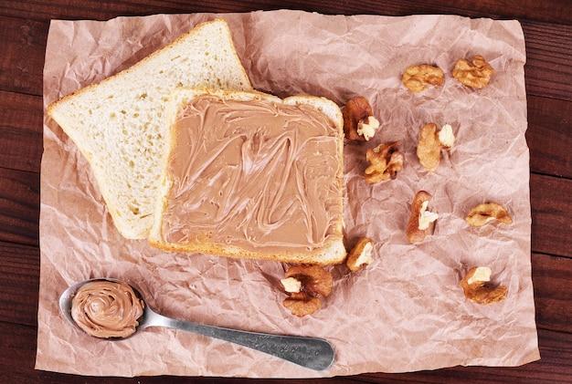 Chleb z czekoladą, orzechami włoskimi i łyżką na papierowym tle