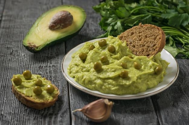 Chleb z guacamole i zielonym groszkiem na drewnianym stole. dieta wegetariańska meksykańskie jedzenie awokado. surowe jedzenie.