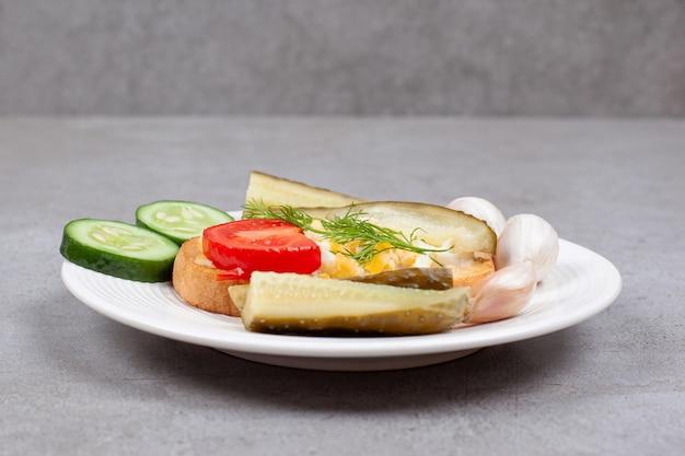 Chleb z jajecznicą i piklami na białym talerzu