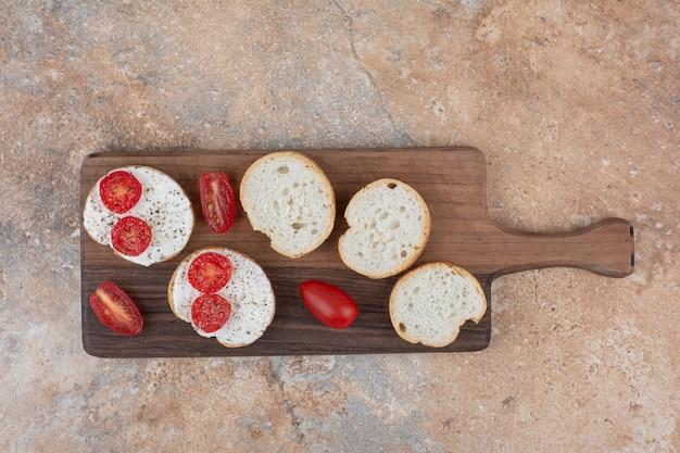 Chleb z kremem i plastrami pomidora na desce