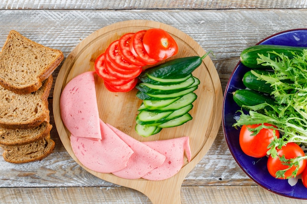 Chleb z pomidorem, ogórkiem, kiełbasą, zieleniną płasko układany na desce do krojenia