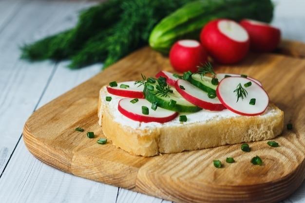 Chleb z twarogiem świeży ogórek rzodkiewki na drewnianej desce do krojenia koncepcja zdrowego śniadania fitness