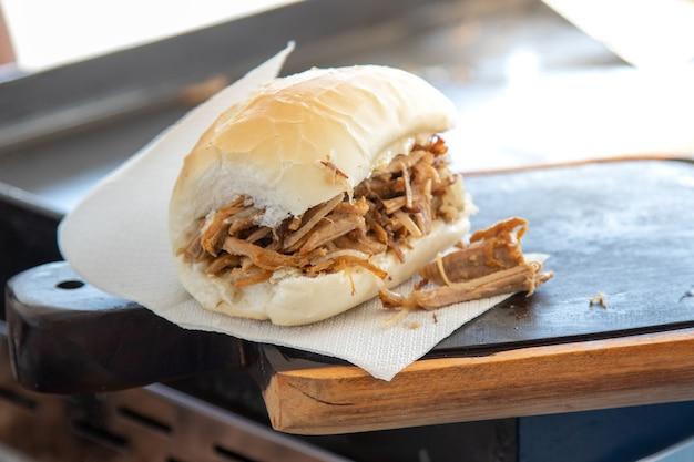Chleb z wołowiną i wieprzowiną na grillu i drewnianej desce. kanapka chlebowa faszerowana grillowanym mięsem, cebulą, masłem i serem. uliczne jedzenie.