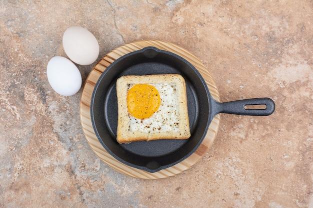 Chleb ze smażonymi jajkami na czarnej patelni z surowymi jajkami