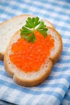 Chleb ze świeżym serem i czerwonym kawiorem na stole.
