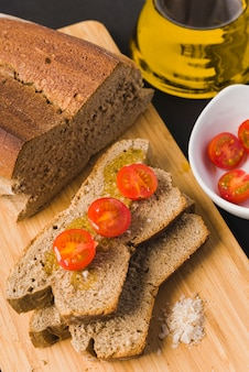 Chleb żytni, kromki chleba z pomidorkami cherry, oliwą i solą, pomidory cherry, olej i sól
