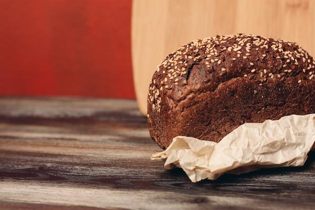 Chleb żytni na stojaku na papier i tablica w ścianie.