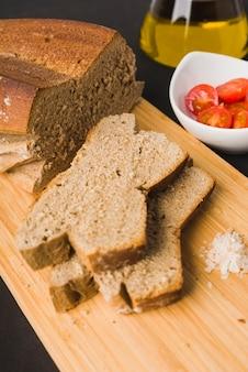 Chleb żytni, plasterki chleba, pomidory cherry, olej i sól na desce do krojenia