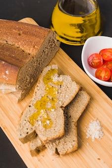 Chleb żytni, plasterki chleba z oliwą i solą, pomidory cherry, olej i sól na desce do krojenia