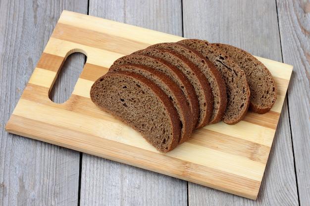 Chleb żytni, pocięty na kawałki, leży na desce do krojenia na stole.