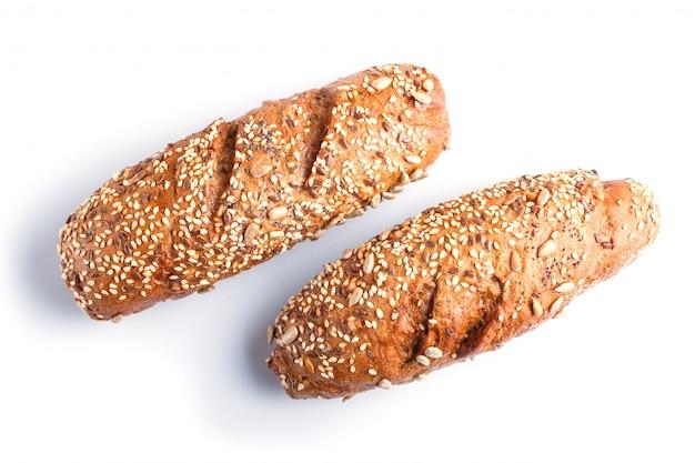 Chleb żytni z nasion słonecznika, sezamu i lnu na białym tle.