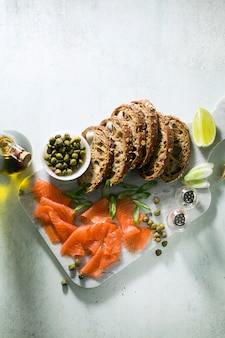 Chleb żytni z wędzonym łososiem na marmurowej desce. zimowa przekąska.
