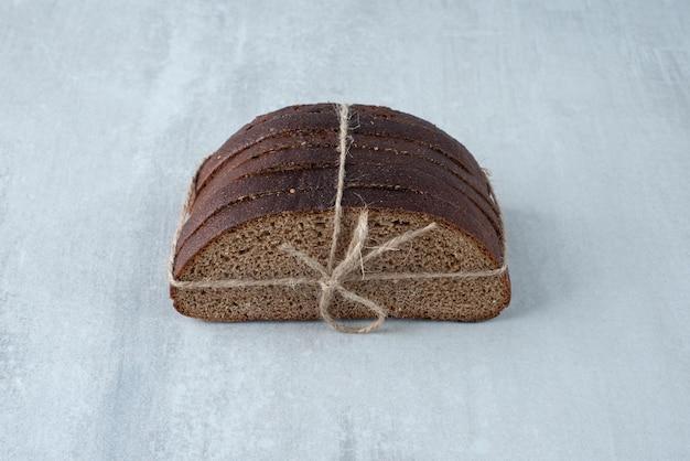 Chleb żytni związany z kamienną powierzchnią liny.