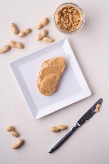 Chlebowa masło orzechowe kanapka na białym kwadratowym kształcie orzeszków ziemnych orzechowym stołowym nożem na powierzchni