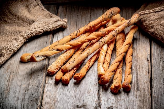 Chlebowi kije na drewnianym tle. zdrowe jedzenie