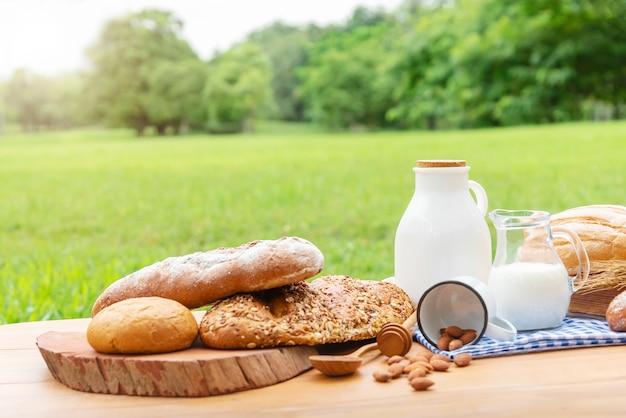 Chleby i mleko na drewno stole z zamazanym zieleni ogródu tłem.