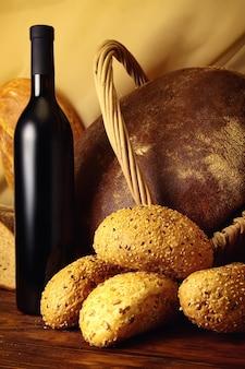 Chleby i wino na drewnianym stole