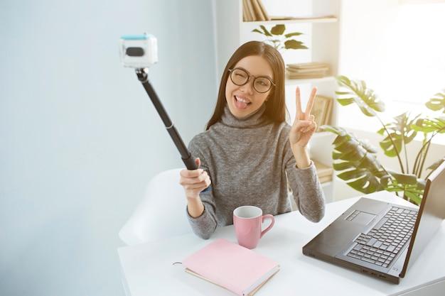 Chłodna brunetka siedzi w jasnym pokoju i bierze selfie w aparacie za pomocą selfie-stick