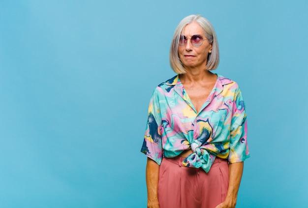 Chłodna kobieta w średnim wieku czująca się nieświadoma, zagubiona i niepewna, którą opcję wybrać, próbując rozwiązać problem