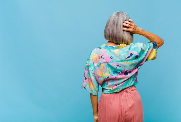 Chłodna kobieta w średnim wieku myśląca lub wątpiąca, drapiąca się po głowie, zdziwiona i zdezorientowana, widok z tyłu lub z tyłu