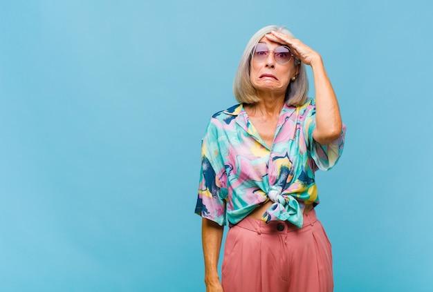 Chłodna kobieta w średnim wieku panikująca z powodu zapomnianego terminu, zestresowana, zmuszająca do zatuszowania bałaganu lub błędu