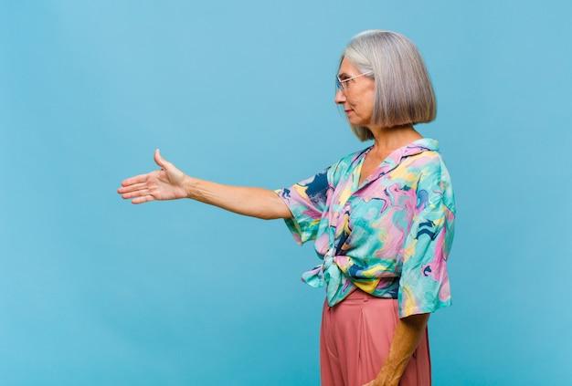 Chłodna kobieta w średnim wieku, uśmiechnięta, witająca się i oferująca uścisk dłoni w celu zawarcia udanej transakcji
