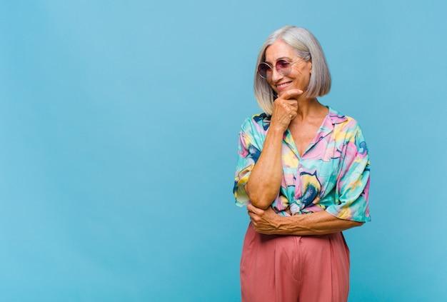 Chłodna kobieta w średnim wieku, uśmiechnięta z radosnym, pewnym siebie wyrazem, z ręką na brodzie, zastanawiająca się i spoglądająca w bok