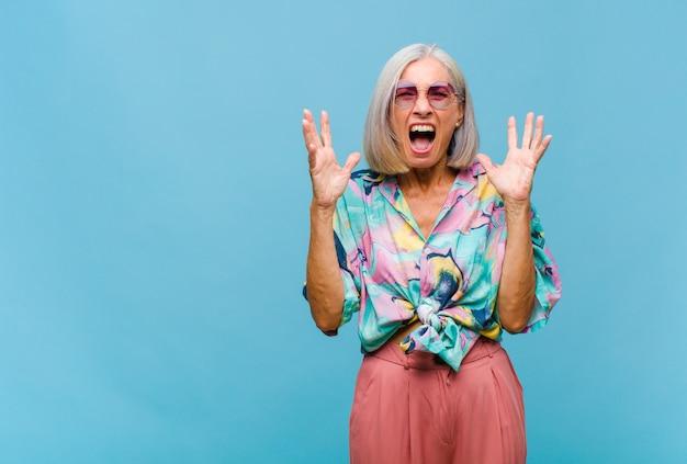 Chłodna kobieta w średnim wieku, wściekle krzycząca, zestresowana i zirytowana, z rękami uniesionymi do góry, mówiąca dlaczego ja