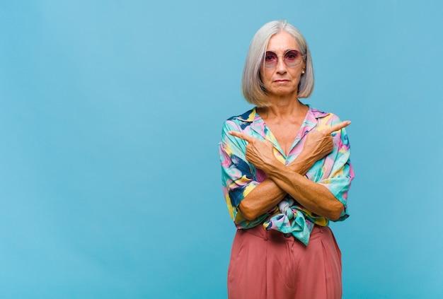 Chłodna kobieta w średnim wieku wyglądająca na zdziwioną i zdezorientowaną, niepewną siebie i wskazującą w przeciwnych kierunkach z wątpliwościami