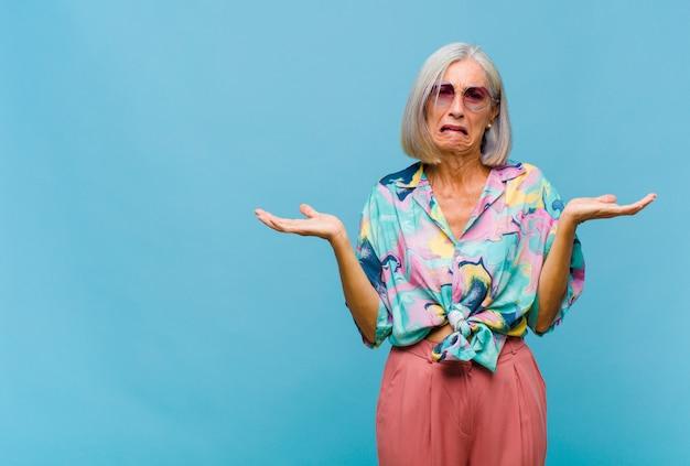Chłodna kobieta w średnim wieku wyglądająca na zdziwioną, zdezorientowaną i zestresowaną, zastanawiającą się między różnymi opcjami i niepewną