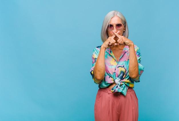 Chłodna kobieta w średnim wieku, wyglądająca poważnie i niezadowolona, z dwoma palcami skrzyżowanymi z przodu z odmową, prosząca o ciszę