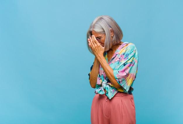 Chłodna kobieta w średnim wieku zasłaniająca oczy dłońmi smutnym, sfrustrowanym wyrazem rozpaczy, płacząca, widok z boku