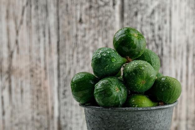 Chłodne figi w mini wiaderku na nieczysty drewnianej ścianie. zbliżenie.