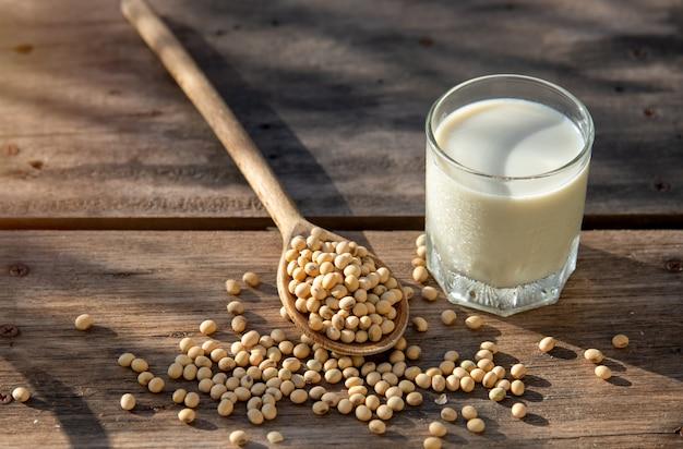 Chłodne mleko sojowe i soja na drewnianym stole z oświetleniem rano
