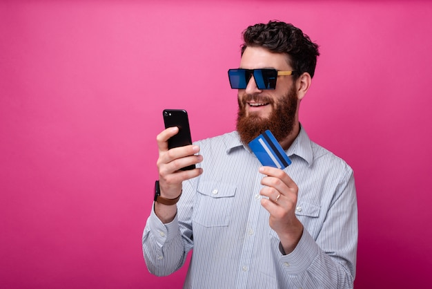 Chłodno brodaty mężczyzna patrzeje jego telefon trzyma jego kartę kredytową jest ubranym okulary przeciwsłonecznych. bankowość internetowa lub zakupy online koncepcja.