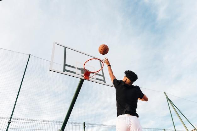 Chłodno sportowy młody człowiek rzuca koszykówkę w obręcz