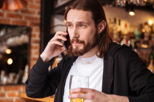 Chłodny brodaty mężczyzna rozmawia przez telefon w pobliżu baru