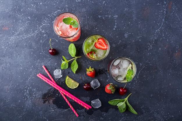 Chłodny napój detoksykujący z truskawkami, limonką, wiśnią i miętą różne letnie lemoniady lub mrożona herbata. koktajle mojito