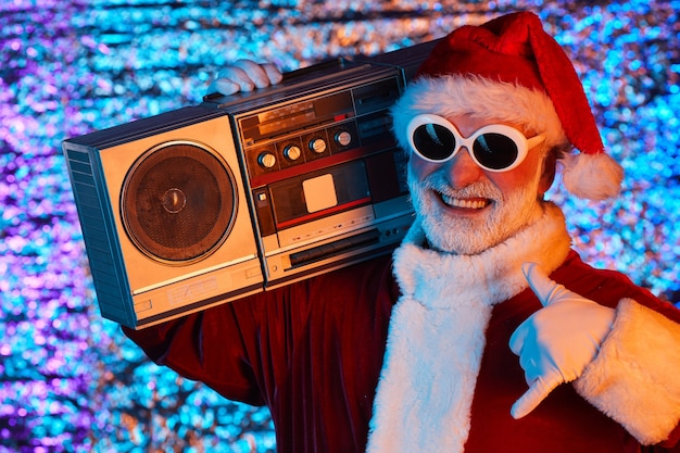 Chłodny święty mikołaj w okularach przeciwsłonecznych, słuchający muzyki na stereo i dobrze się bawiąc