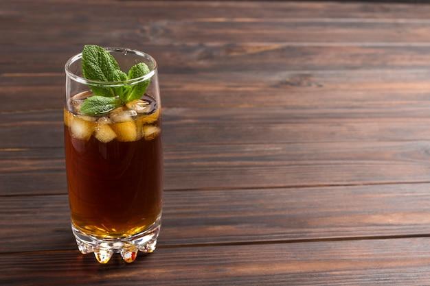 Chłodząca letnia herbata z lodem i miętą. ciemne tło drewna. skopiuj miejsce