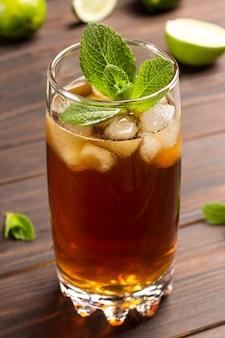 Chłodząca letnia herbata z lodem i miętą. na stole liście limonki i mięty.