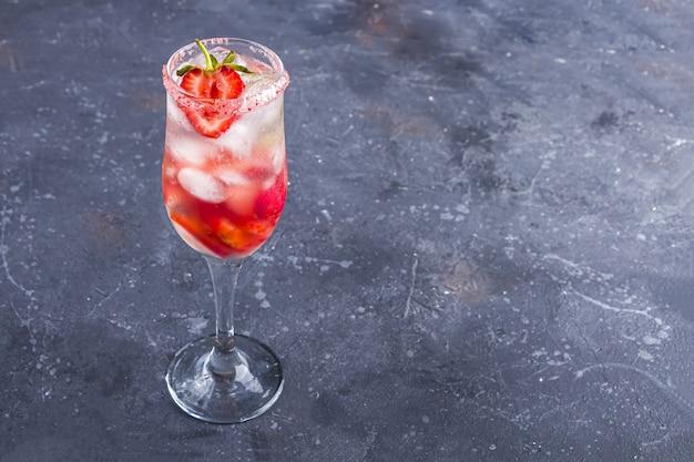 Chłodząca sangria truskawkowa z winem, truskawką, kostkami lodu w kieliszku do szampana