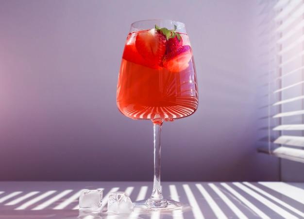 Chłodząca truskawkowa sangria z winem musującym, truskawką, kostkami lodu w kieliszku do szampana