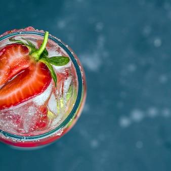 Chłodzący włoski koktajl alkoholowy rossini z winem musującym, truskawką, kostkami lodu w kieliszku szampana