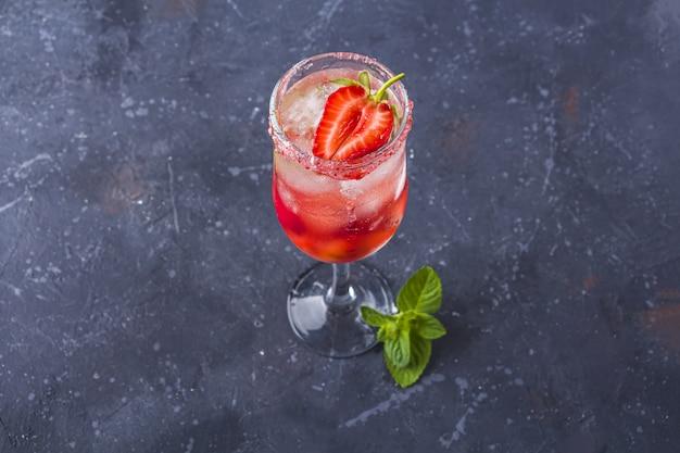 Chłodzący włoski koktajl alkoholowy rossini z winem musującym, truskawkami, kostkami lodu w kieliszku do szampana.