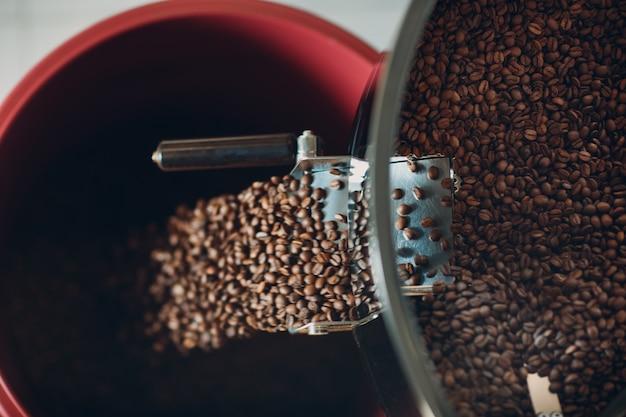 Chłodzenie kawy w palarce podczas procesu palenia kawy. młoda kobieta pracownik barista mieszanie i wylewa ziarna kawy.