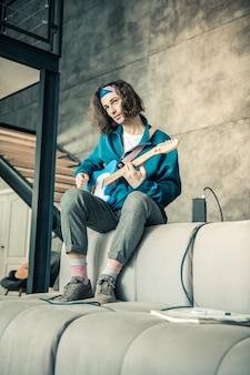 Chłodzenie na kanapie. ciekawy, przystojny młody muzyk uczący się nowych akordów i technik, niosąc uroczą gitarę