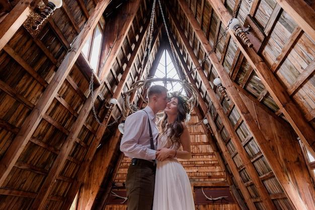 Chłopak całuje dziewczynę w sukience, ubraną w strój ślubny wewnątrz drewnianego budynku, zakochaną parę